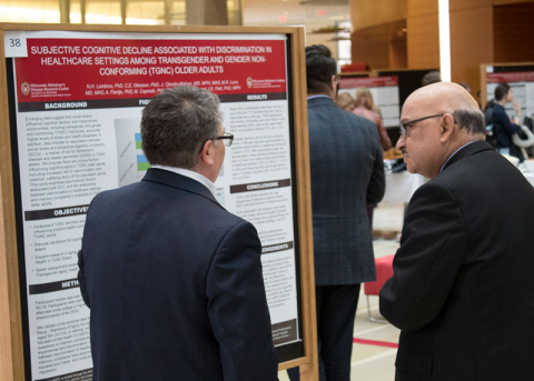 scientists talking in front of a research poster