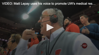 sports announcer matt lepay wearing a headset and cheering at a Wisconsin Badgers basketball game