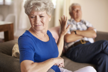 woman visibly upset with man sitting on couch next to her